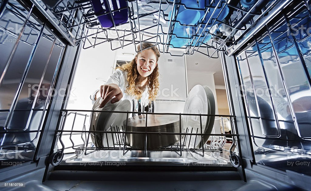 Looking out from dishwasher interior at young woman loading dishes stock photo