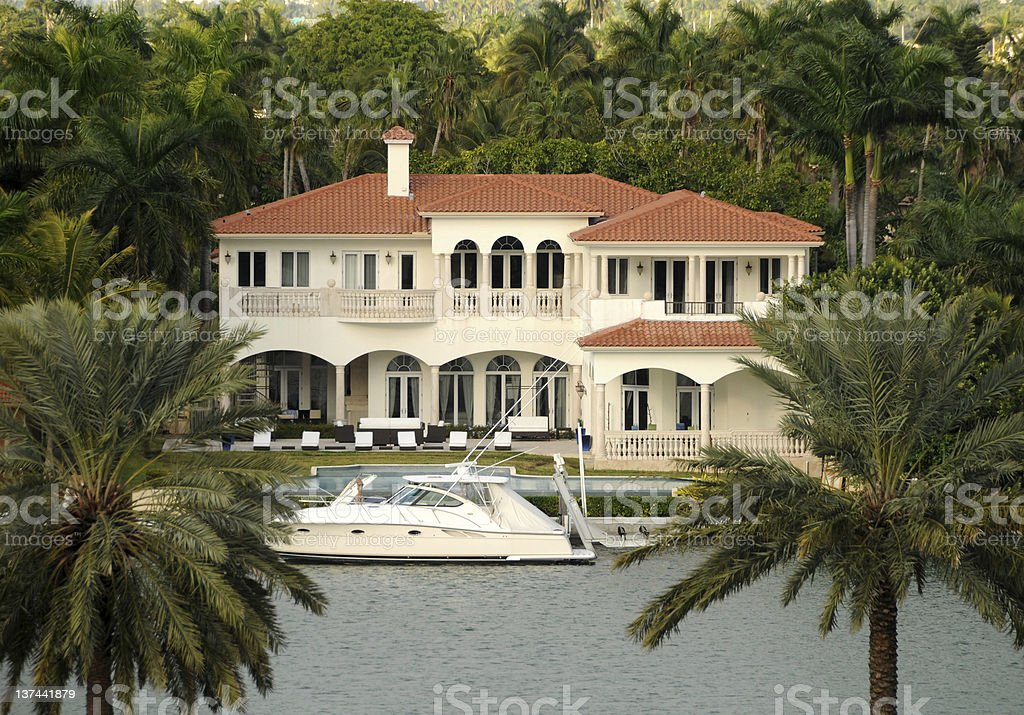 Looking over the lake to a mansion and yacht stock photo