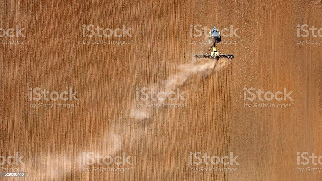 Looking straight down on farming tractor planting springtime fields. stock photo