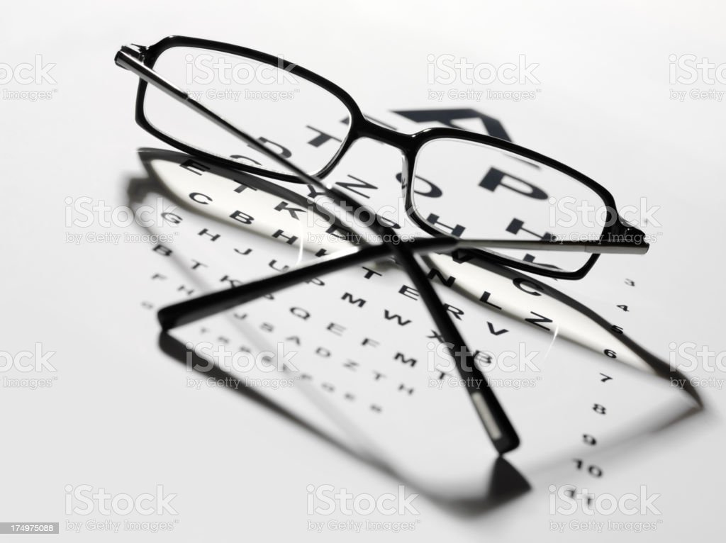 Looking through Black Rimed Glasses at a Eye Test Chart stock photo