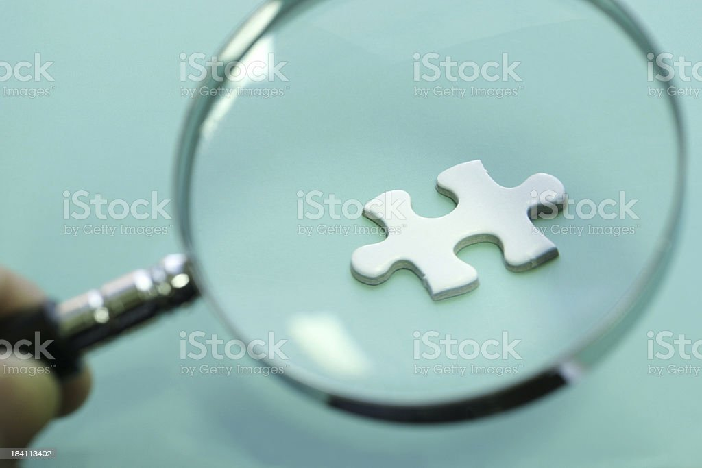 Looking Through Magnifying Glass to a Puzzle royalty-free stock photo