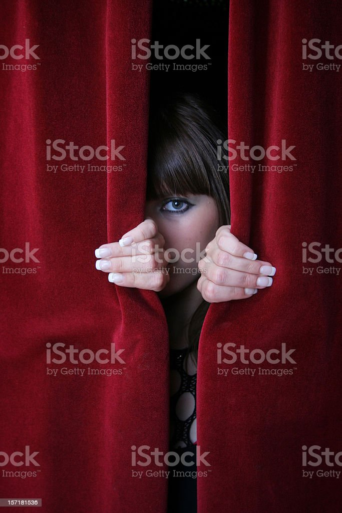 Looking through red curtains stock photo
