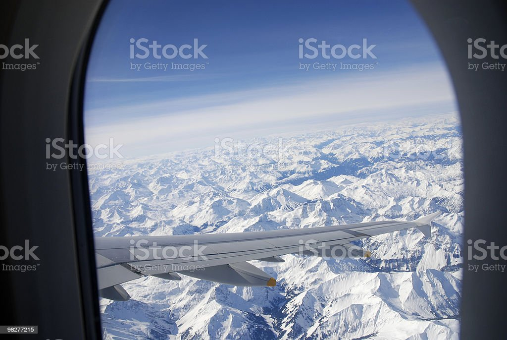 looking through window on flight over the snowcovered Alps