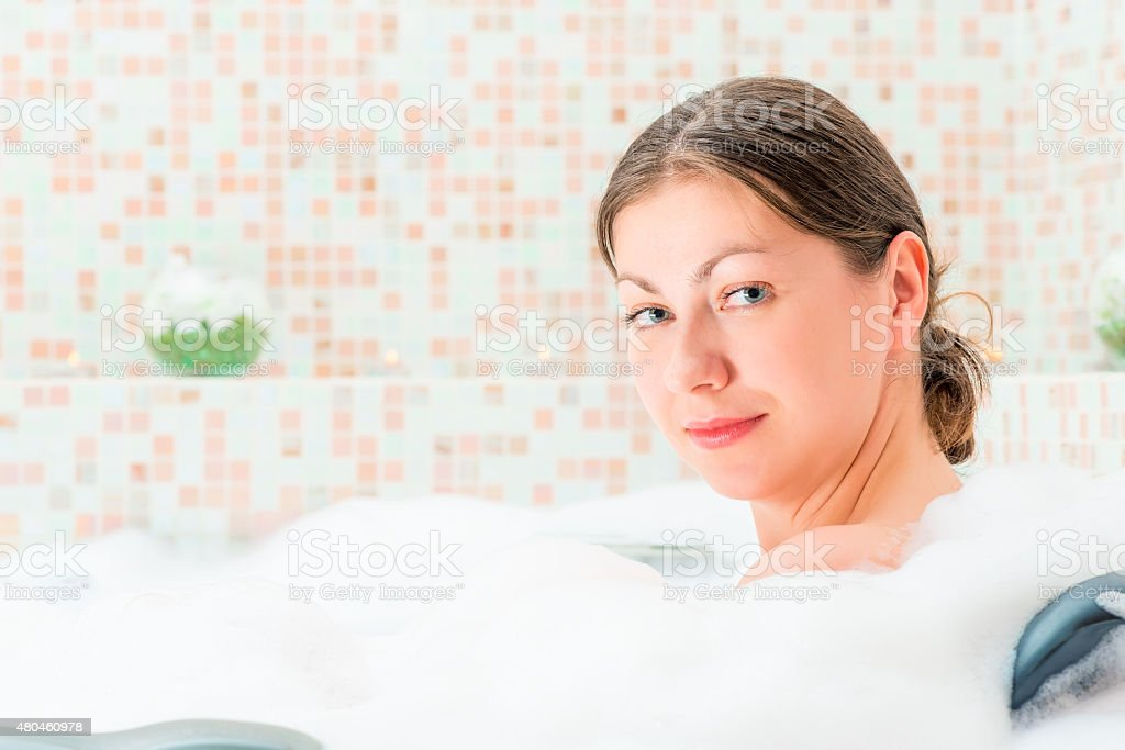 looking to the camera girl sitting in the bath stock photo