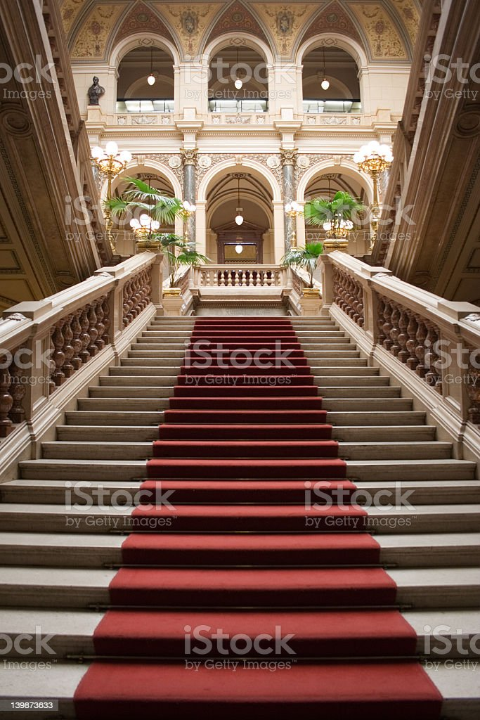 Looking up a red carpet stairway in a grand columned room  stock photo