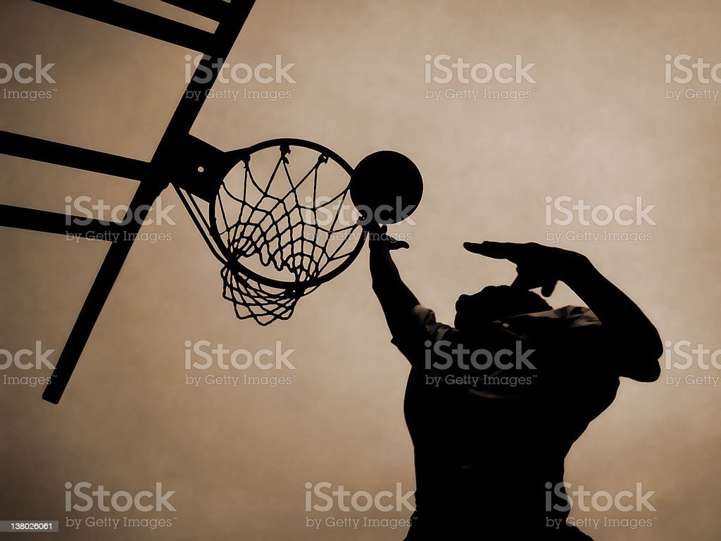 Looking up at a man jumping up to put basketball in a net stock photo