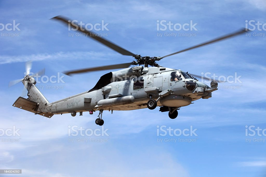 Looking up at a Seahawk helicopter flying in blue sky stock photo