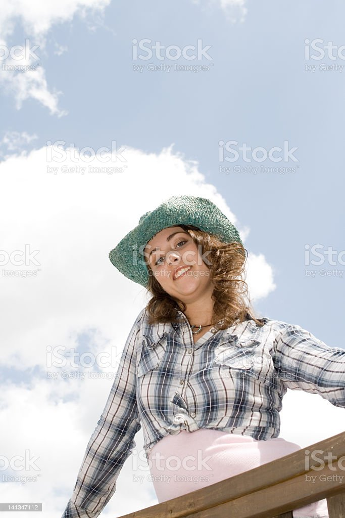 Looking up at Cowgirl Against Clouds and Blue Sky stock photo
