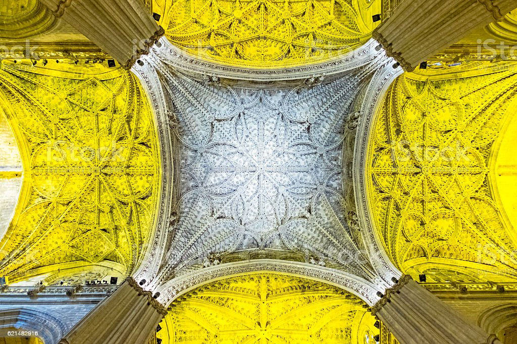 Looking up at Seville Cathedral illuminated ceiling detail stock photo