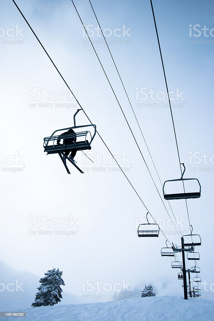 Looking Up at Skier Riding Ski Lift on Mountain royalty-free stock photo