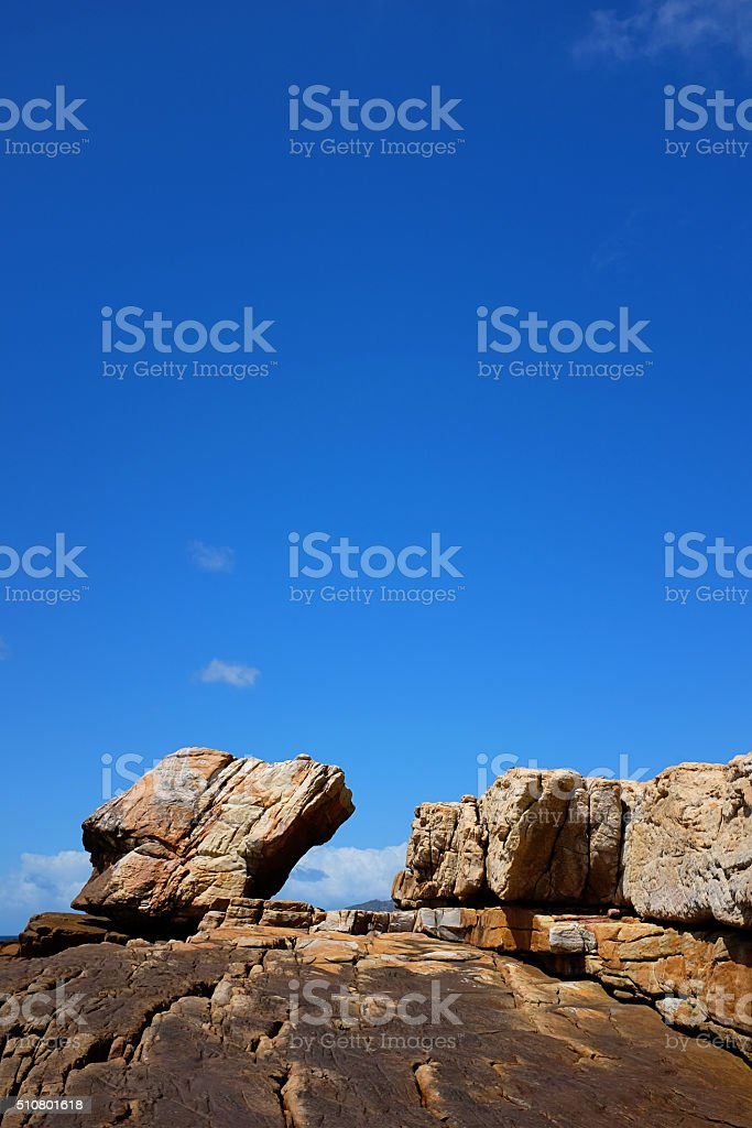 Looking up cliff face at rocks and clear sky stock photo