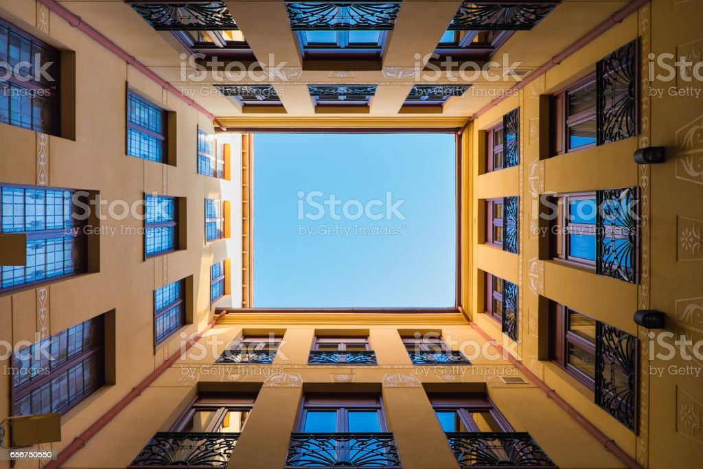 Looking up the sky between old building walls stock photo