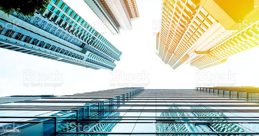 Looking up view of skyscraper reflect blue sky, sun stock photo