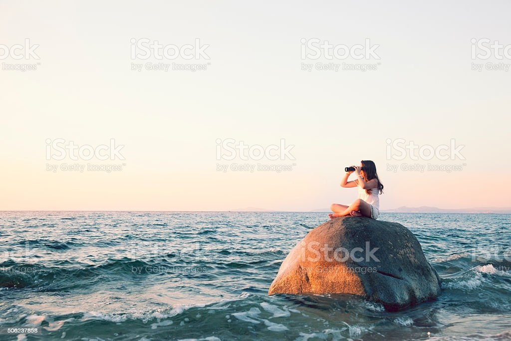 Looking with binoculas on top of a bouder stock photo