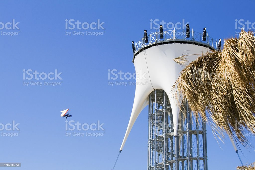 Lookout tower and paraglider over blue sky stock photo