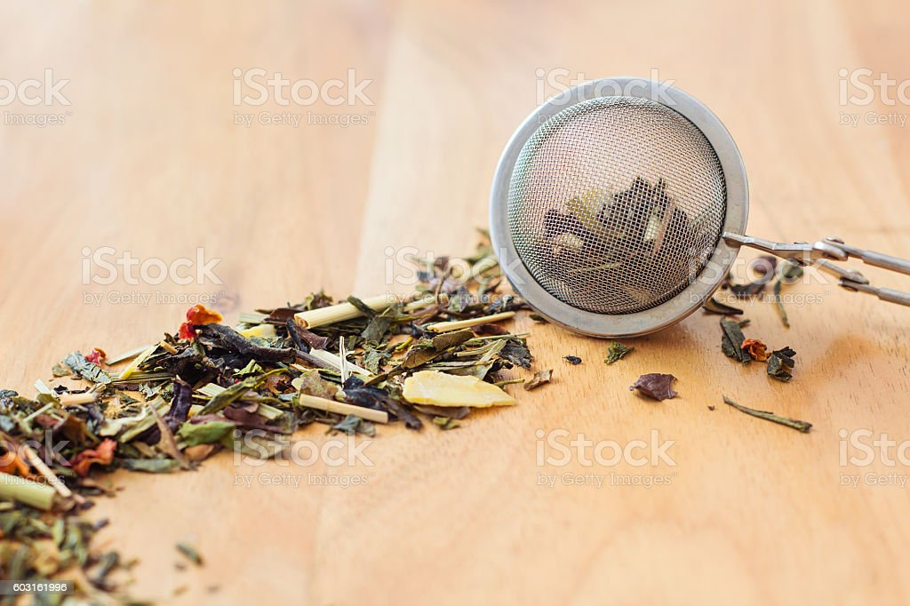 Loose leaf tea and tea strainer on wooden background stock photo