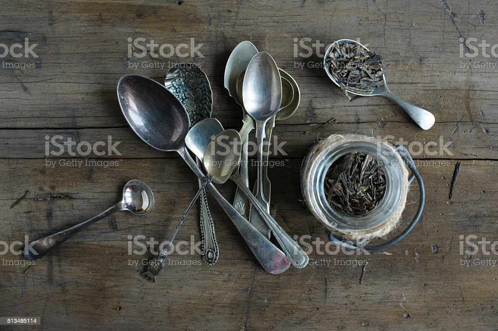 Loose leaf tea in jar, with tarnished spoons stock photo