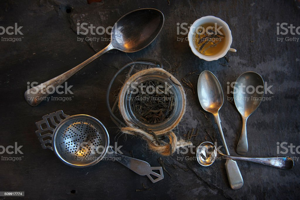 Loose leaf tea in jar, with teacup and spoons stock photo