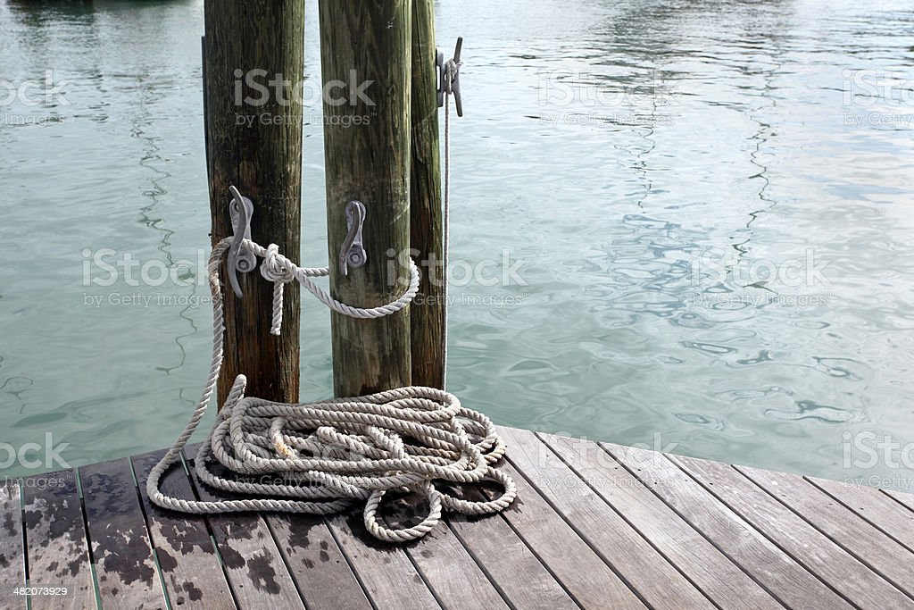 Loosely coiled rope on weathered wooden dock.  Harbor.  Copy space. royalty-free stock photo