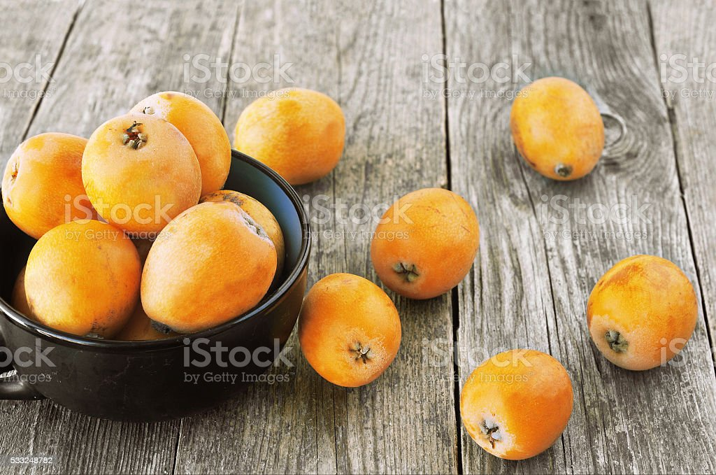 loquats on wooden background stock photo