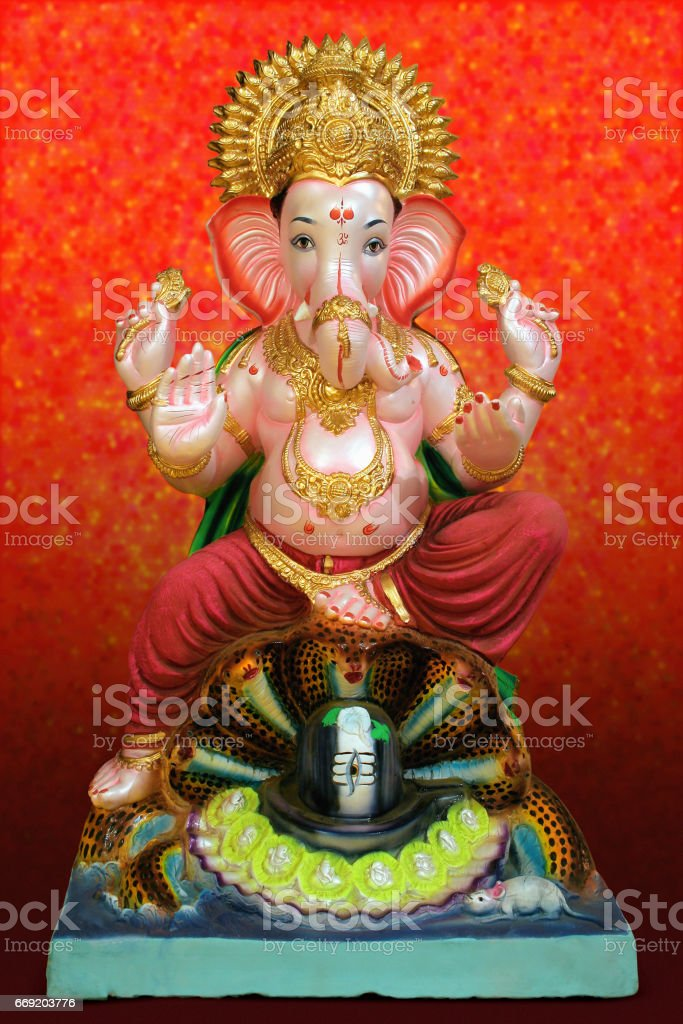 Lord Ganesha idol on red background stock photo