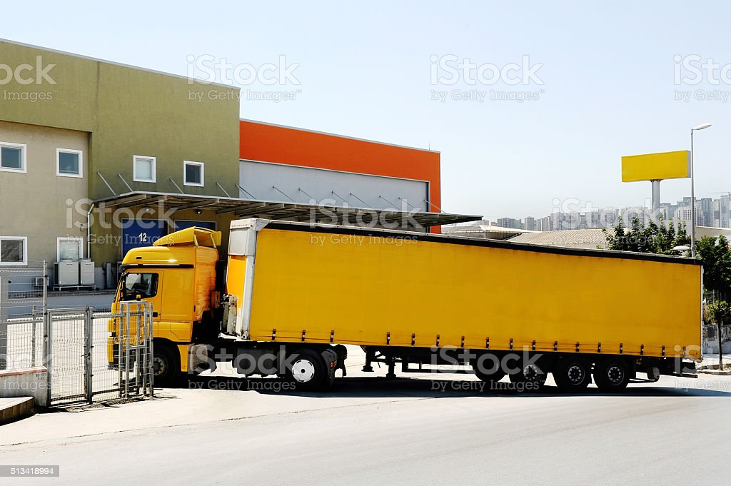 Lorry approaching warehouse stock photo