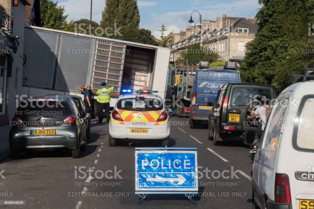 Lorry stuck on steep hill with driver, police and sign stock photo