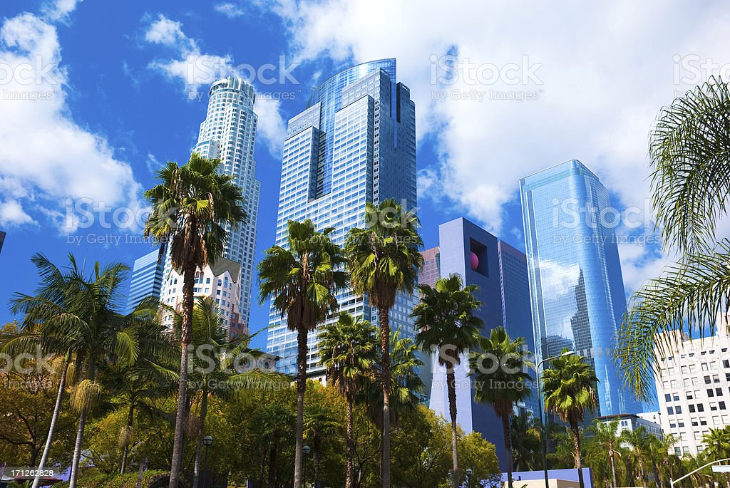 Los Angeles skyscrapers, clouds, and palm trees stock photo