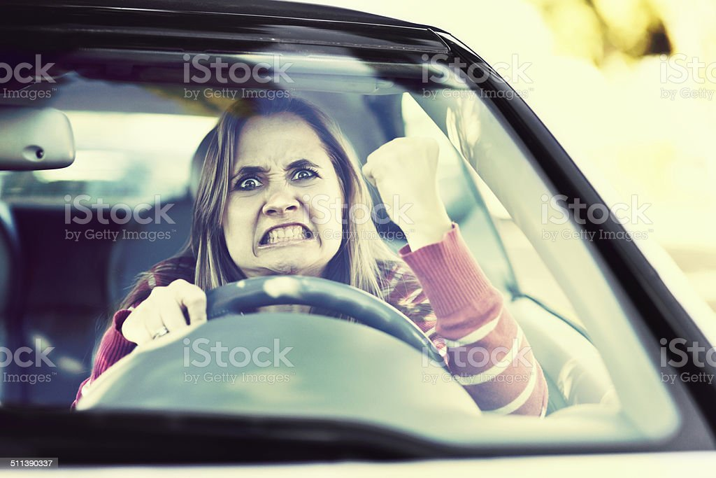 Losing her temper, a woman driver shakes fist through windshield stock photo