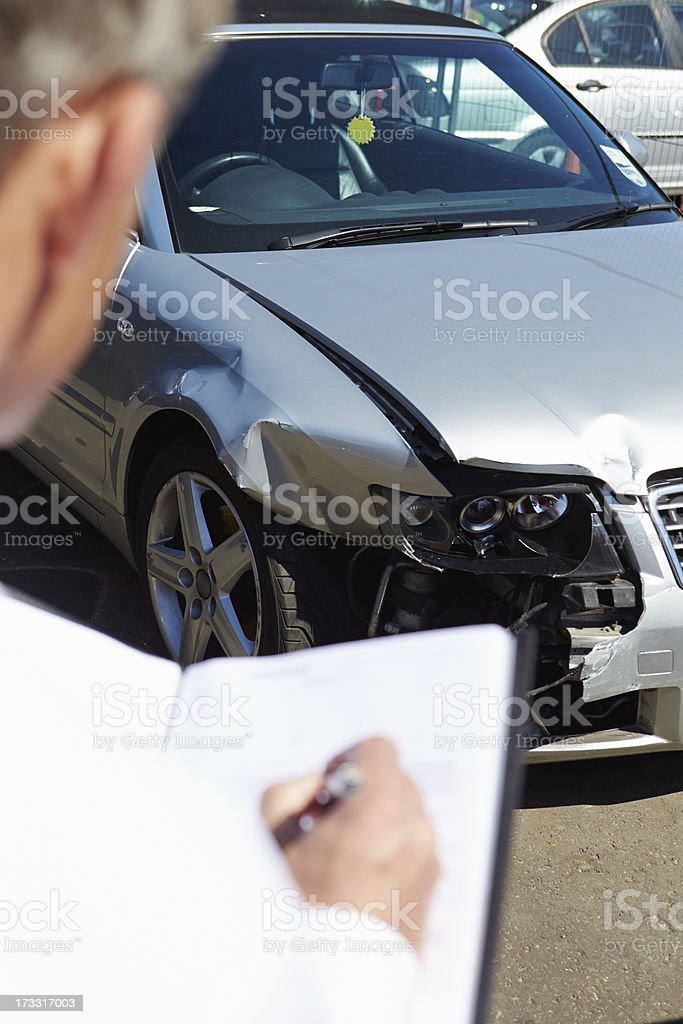 Loss Adjuster Inspecting Car Involved In Accident royalty-free stock photo
