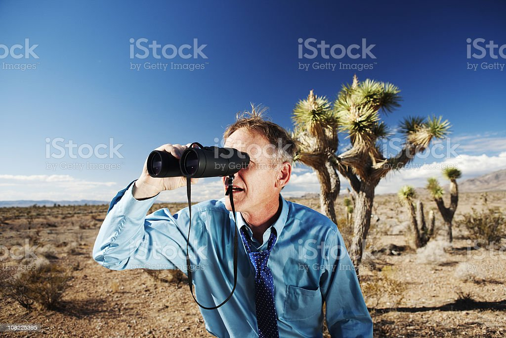 Lost businessman in desert looking for direction using binoculars stock photo