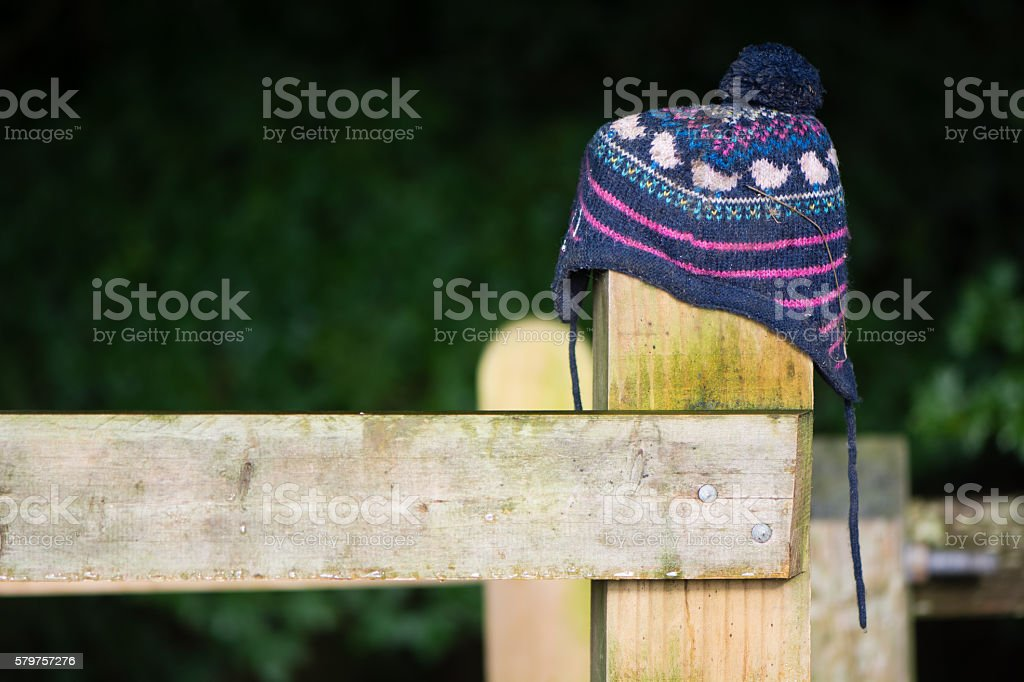 Lost hat on wooden fence post stock photo
