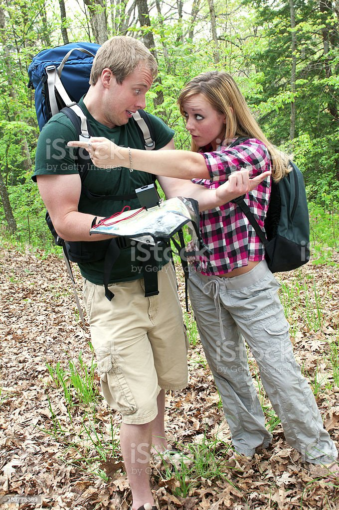 Lost hikers in the forest arguing about direction - V royalty-free stock photo