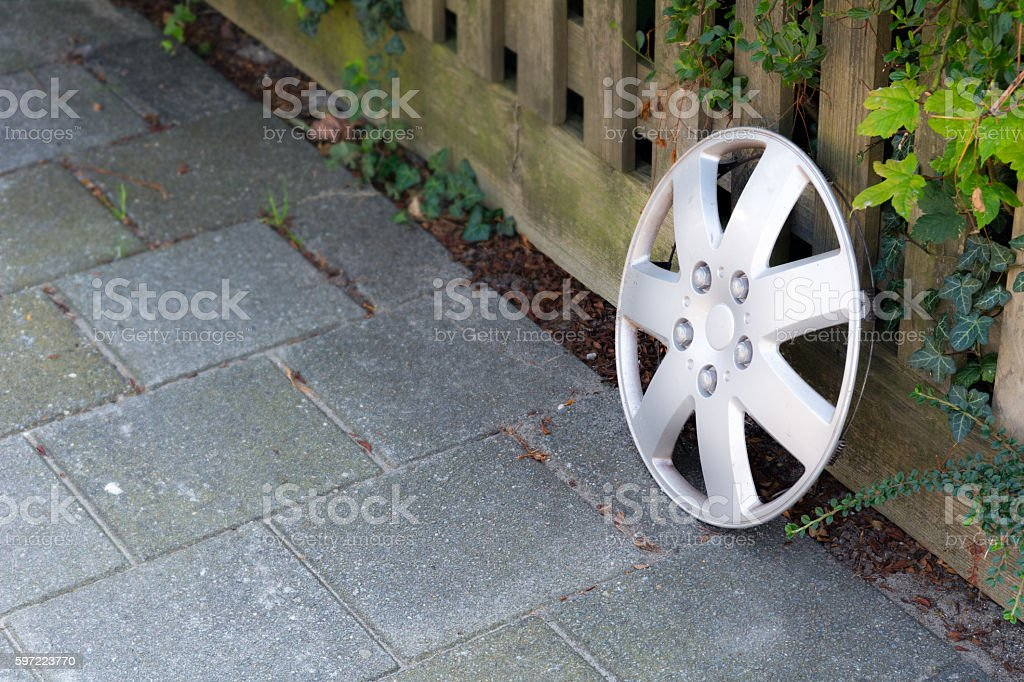 lost hubcap on the edge of the garden fence stock photo