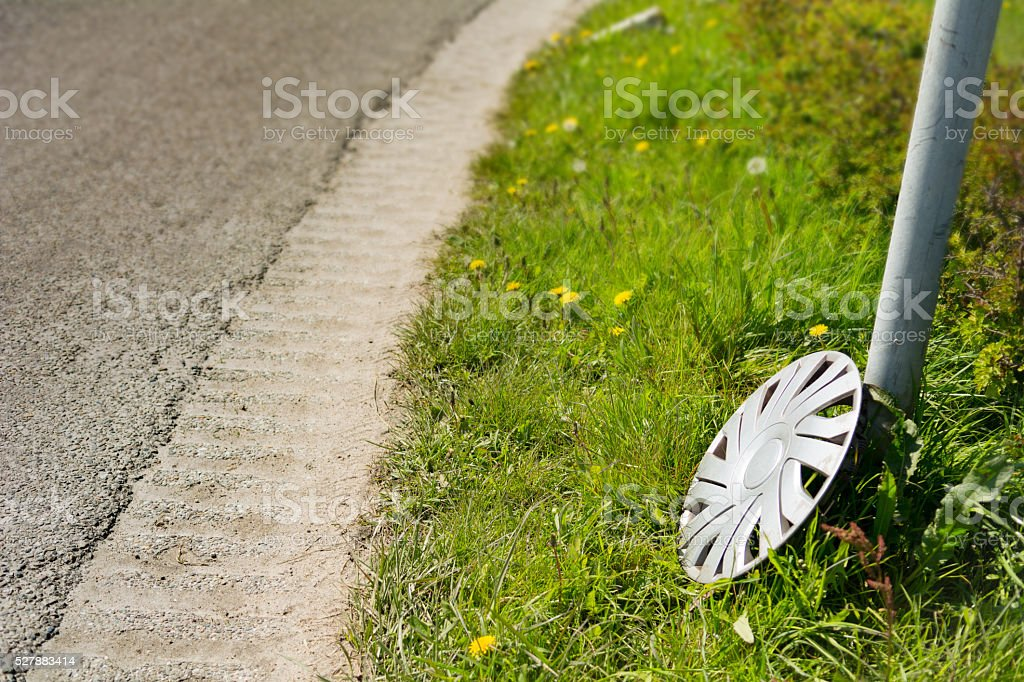 lost hubcap on the edge of the road stock photo