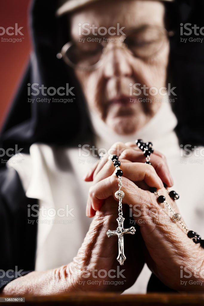 Lost in prayer, an old nun clasps a rosary stock photo