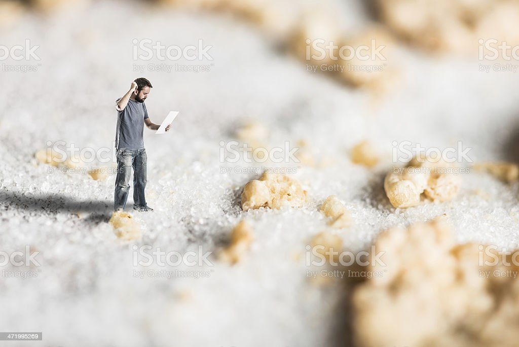 Lost man looking at map in micro world of sugar stock photo