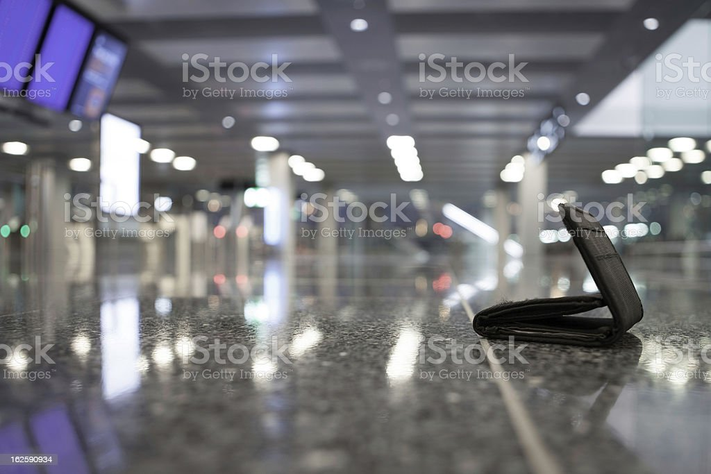 A lost wallet in a blurry airport stock photo