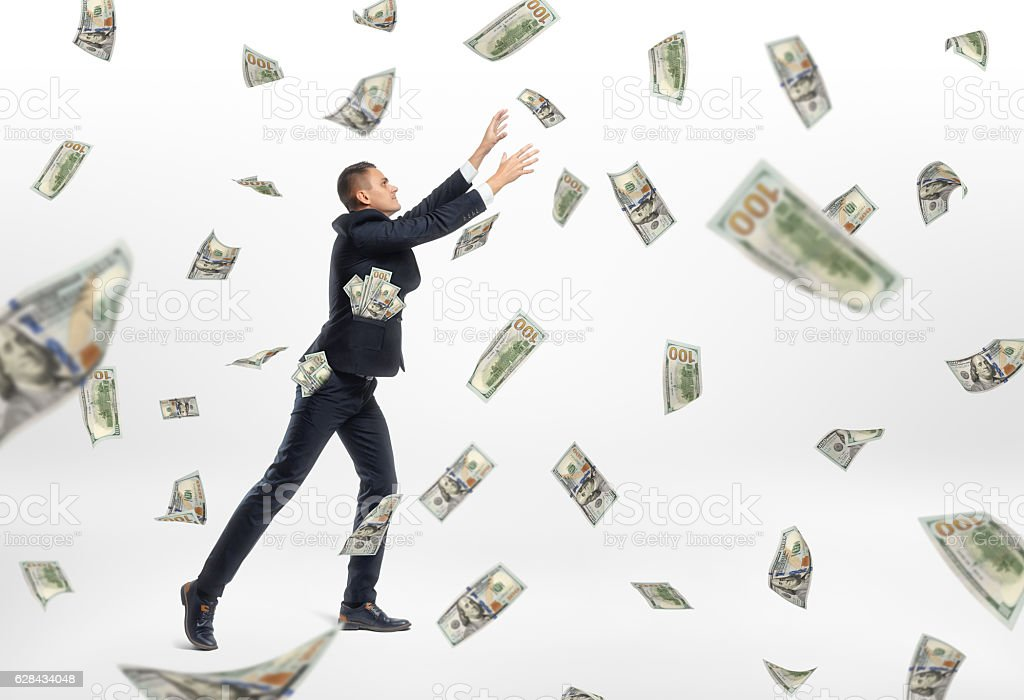 Lot of cash money flying and businessman catching them stock photo