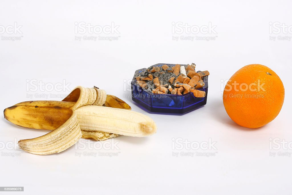 Lot of cigarettes in the ashtray, banana and orange stock photo