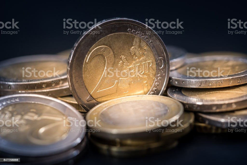 lot of euro coins with reflection on black table. stock photo