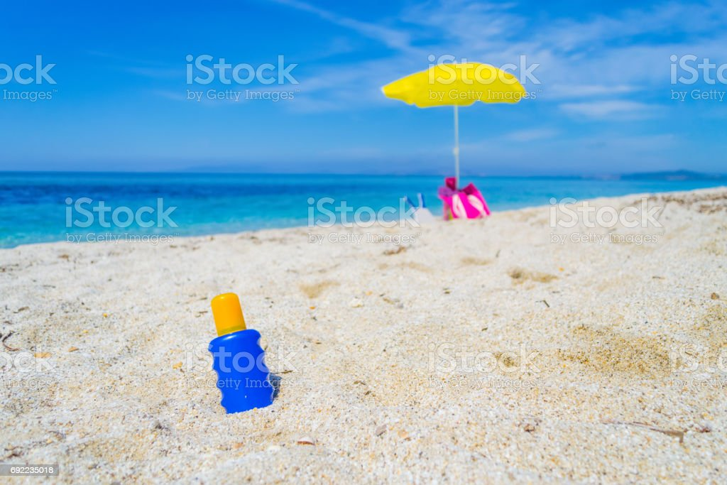lotion bottle and beach umbrella on the sand stock photo