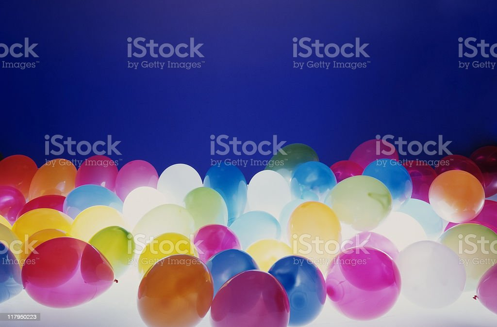 Lots of balloons against blue background with light from bottom stock photo