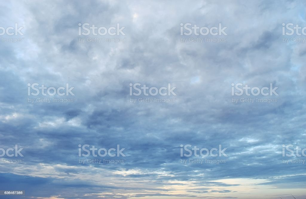 Lots of clouds moving in the blue sky stock photo