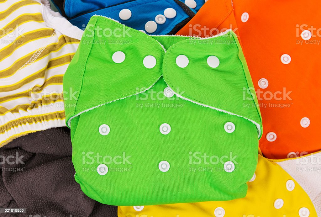 Lots of colorful eco-friendly diapers are scattered. stock photo
