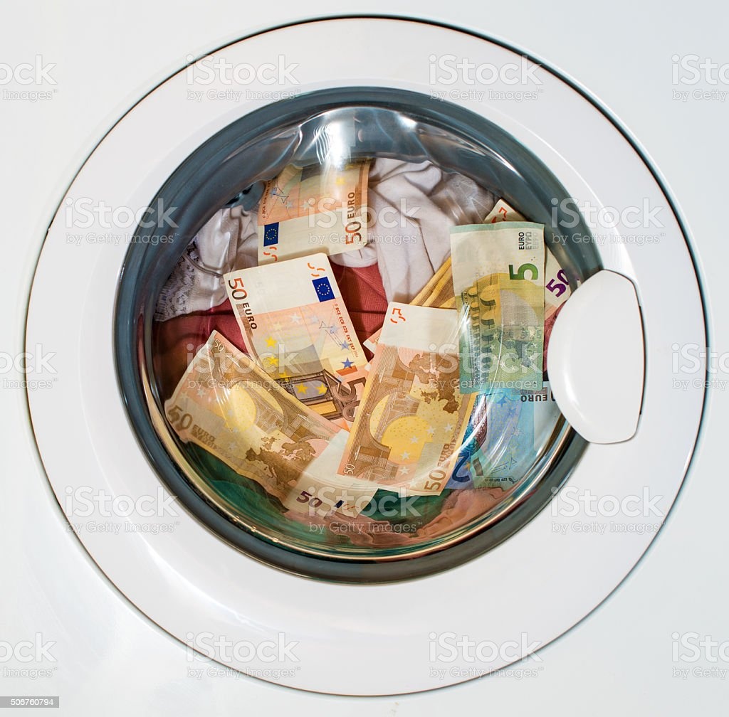 Lots of euros in washing machine. Dirty money concept. stock photo