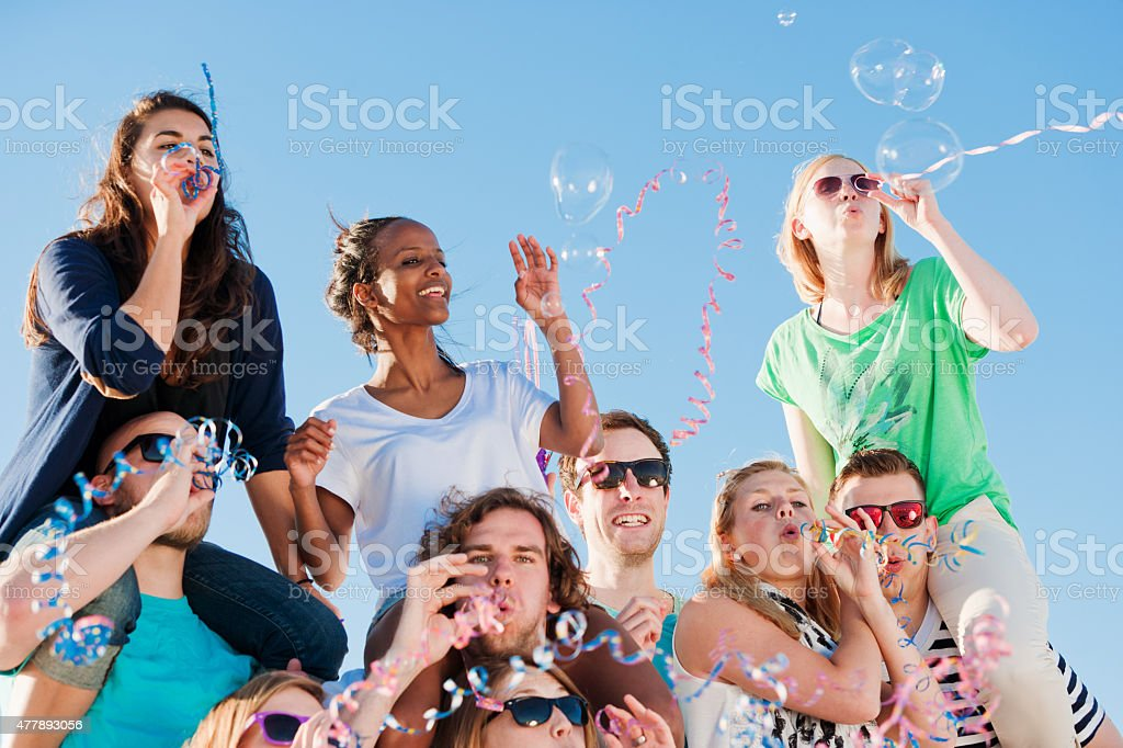 Lots of friends enjoying a beach party in summer time stock photo