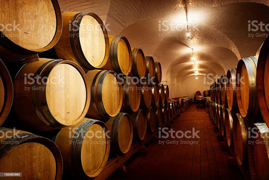 Lots of future wine! Oak barrels maturing in winery cellar royalty-free stock photo