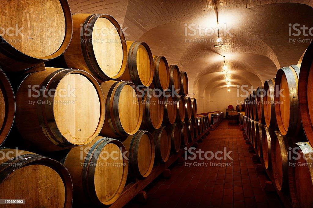 Lots of future wine! Oak barrels maturing in winery cellar stock photo