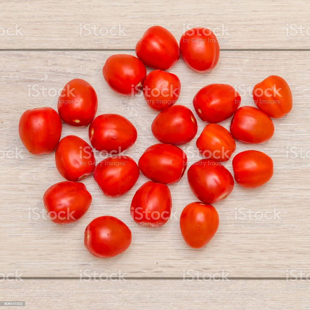 Lots of tomatoes on a wooden table, top view stock photo